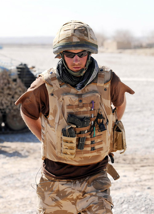 Prince Harry carries a 9mm pistol and wears body armour in the desert in Helmand Province